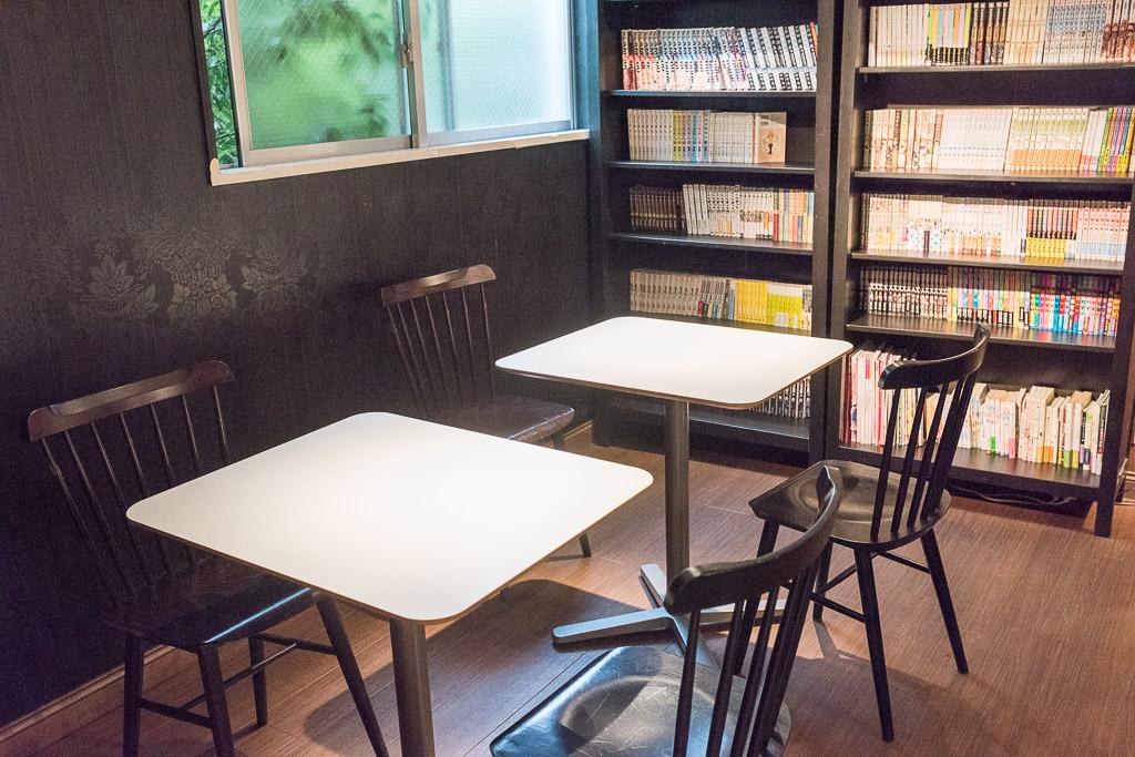 猫カフェ・きゃらふのテーブル席と漫画本の棚